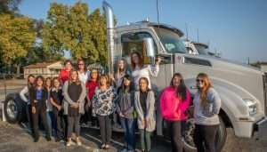 Women from Palmer Trucks' Kenworth of Indianapolis - West facility stand in celebration alongside a new Kenworth T880.